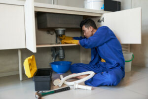 asian-plumber-blue-overalls-clearing-blockage-drain_1098-17773